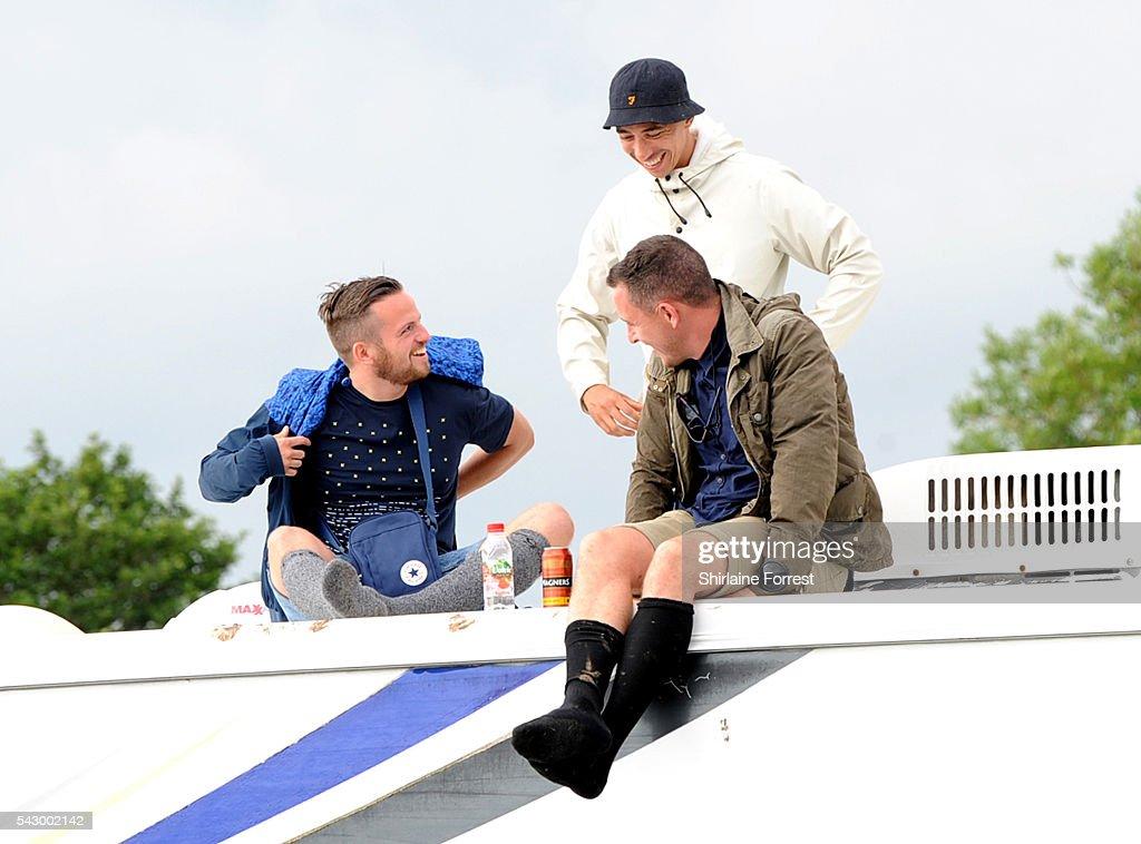 Festival crew escape the mud atop a campervan at Glastonbury Festival 2016 at Worthy Farm, Pilton on June 25, 2016 in Glastonbury, England.