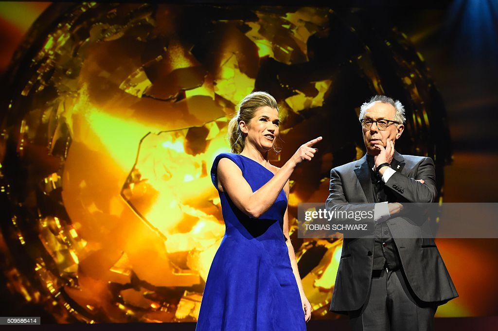 Festival director Dieter Kosslick (R) and Anke Engelke take the stage prior to the film 'Hail, Caesar!' screening as opening film of the 66th Berlinale Film Festival in Berlin on February 11, 2016. Eighteen pictures will vie for the Golden Bear top prize at the event which runs from February 11 to 21, 2016. / AFP / TOBIAS SCHWARZ