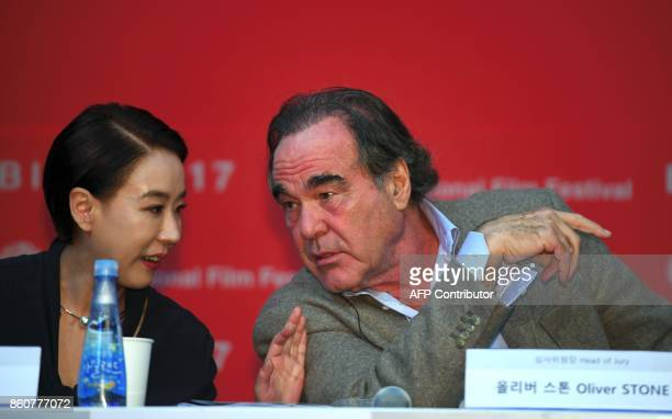 Festival director Kang SooSyoun chats with US director Oliver Stone during a press conference of the New Currents Jury for the 22nd Busan...
