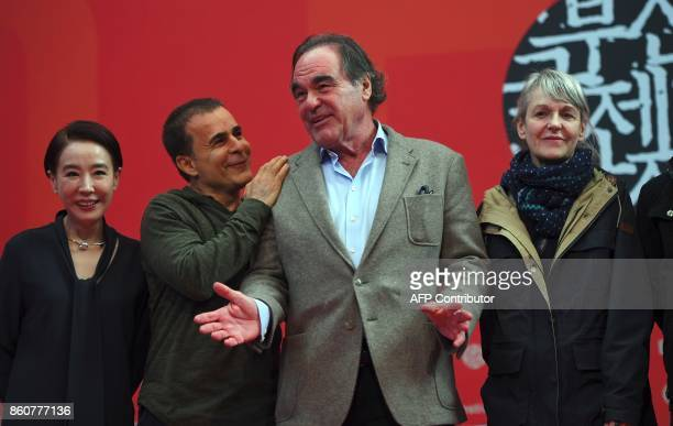 Festival director Kang SooSyoun Iranian director Bahman Ghobadi US director Oliver Stone and French cinematographer Agnes Godard pose for photographs...