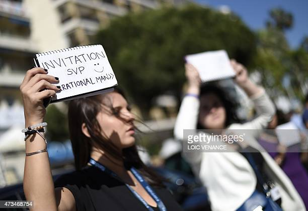 A festival goer holds a cardboard outside the Festival palace asking for an invitation for the film 'Irrational Man' during the 68th Cannes Film...