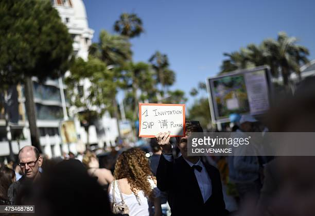 A festival goer holds a cardboard outside the Festival palace asking for an invitation during the 68th Cannes Film Festival in Cannes southeastern...