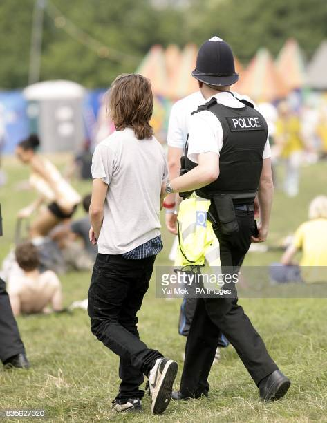 A festival goer is escorted away by a Police officer at the 2009 Glastonbury Festival at Worthy Farm in Pilton Somerset