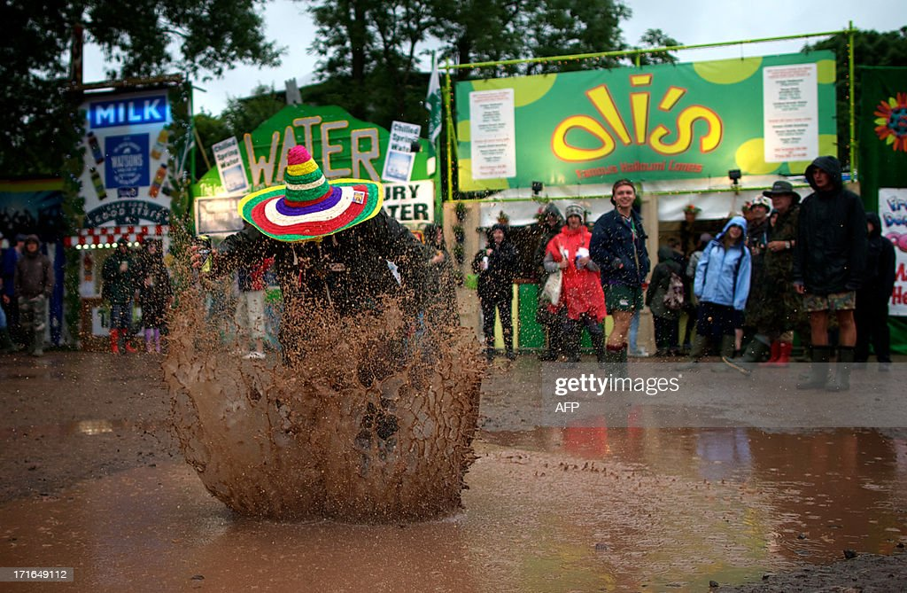 A festival goer jumps in a mud puddle on the second day of the Glastonbury Festival of Contemporary Performing Arts near Glastonbury, southwest England, on June 27, 2013. The festival attracts 170,000 party-goers to the dairy farm in Somerset, and this year's tickets sold out within two hours of going on sale. The Rolling Stones will perform at the festival for the first time, headlining on Saturday night. AFP PHOTO/ANDREW COWIE