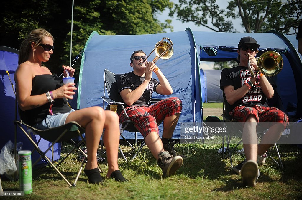 A festival goer looks on as the New York Brass Band performs in the camp site during 80s Rewind Festival at Scone Palace on July 26, 2013 in Perth, Scotland.