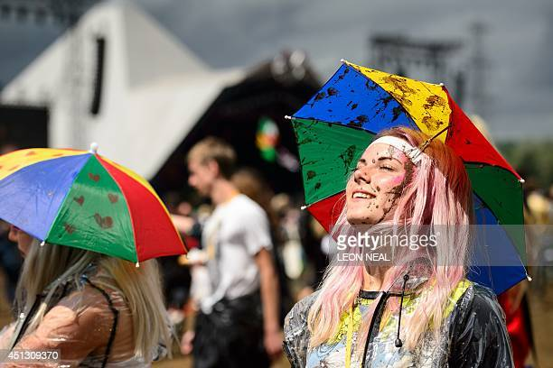 A festival goer looks towards the sun as she stands near to the Pyramid Stage on the first official day of the Glastonbury Festival of Music and...