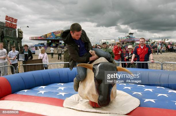 A festival goer rides a mechanical bull during the Oxegen Festival 2008 at the Punchestown Racecourse Naas County Kildare Ireland