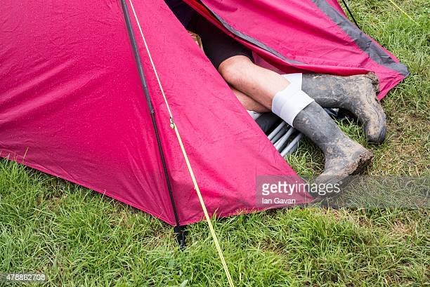 A festival goer shelters from the rain in a tent at the Glastonbury Festival at Worthy Farm Pilton on June 28 2015 in Glastonbury England Now its...
