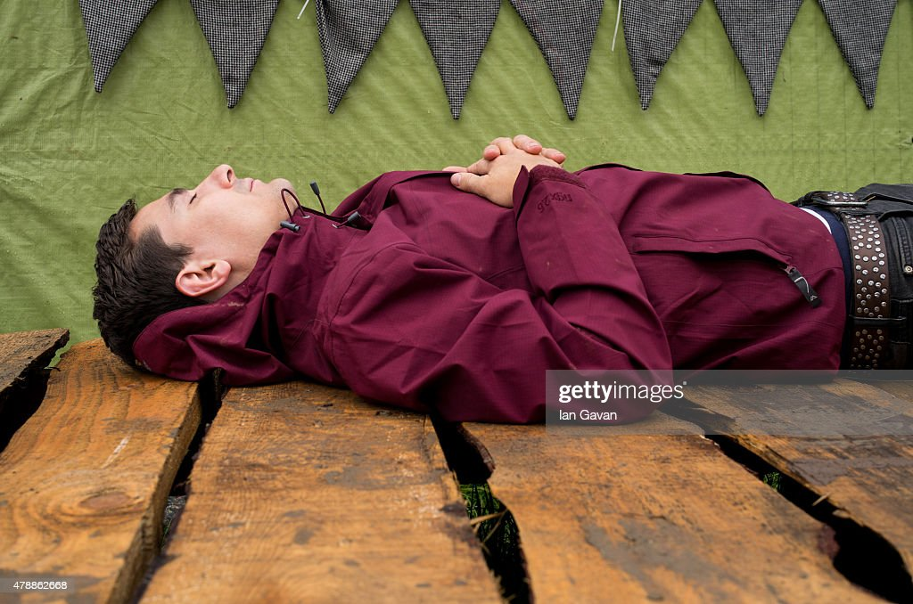 A festival goer sleeps on a table at the Glastonbury Festival at Worthy Farm Pilton on June 28 2015 in Glastonbury England Now its 45th year the...