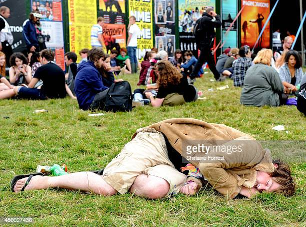 A festival goer sleeps through the artists performing on day 3 of The Leeds Festival at Bramham Park on August 30 2015 in Leeds England
