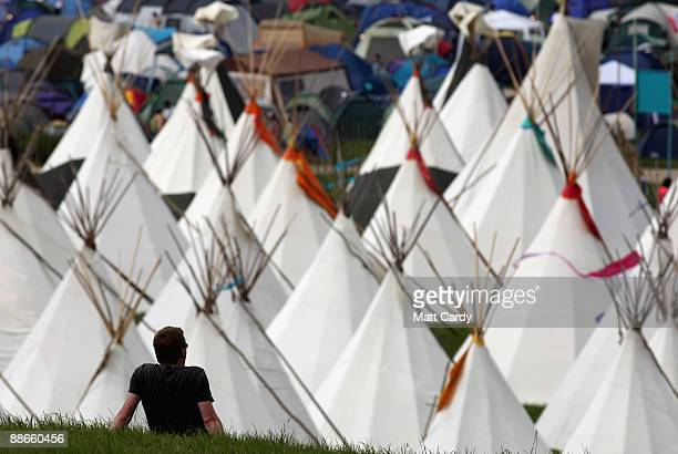 A festival goer takes in the view in front of the tipi field as music fans start to arrive at the Glastonbury Festival site at Worthy Farm Pilton on...