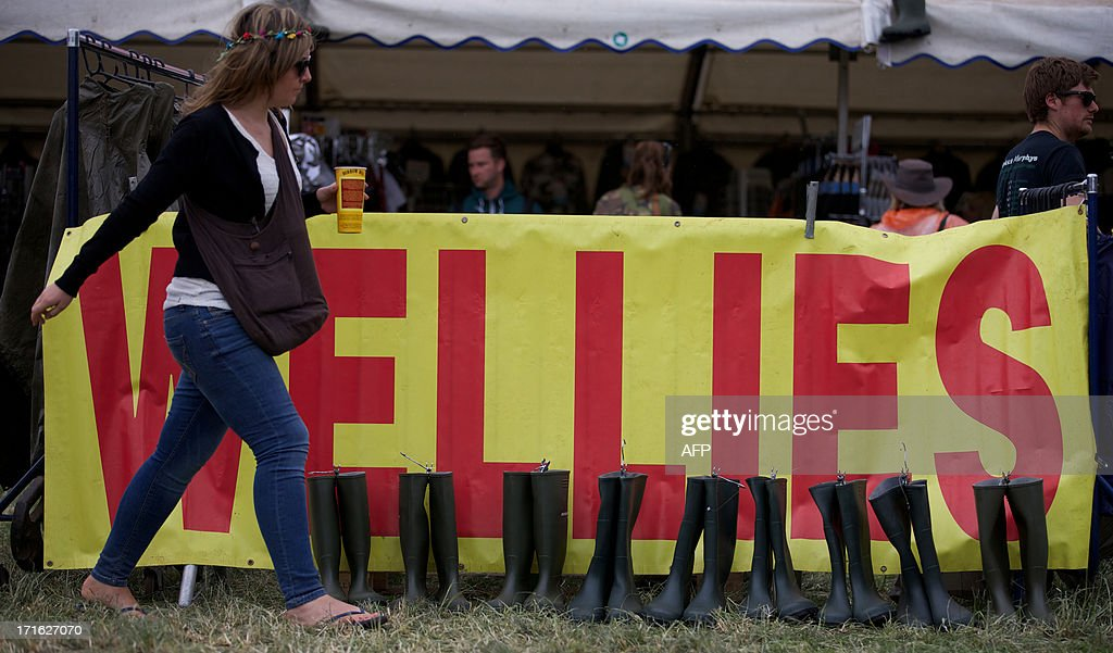 A festival goer walks past a stall selling rubber boots on the second day of the Glastonbury Festival of Contemporary Performing Arts near Glastonbury, southwest England on June 27, 2013. The festival attracts 170,000 party-goers to the dairy farm in Somerset, and this year's tickets sold out within two hours of going on sale. The Rolling Stones will perform at the festival for the first time, headlining on Saturday night.