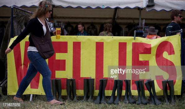 A festival goer walks past a stall selling rubber boots on the second day of the Glastonbury Festival of Contemporary Performing Arts near...