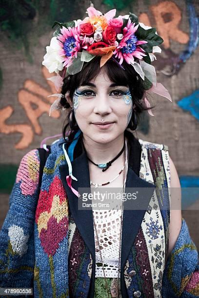 Festival goer wearing a floral head dress at the Glastonbury Festival at Worthy Farm Pilton on June 28 2015 in Glastonbury England
