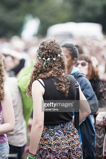 Festival goer wearing a floral head dress at the Glastonbury Festival at Worthy Farm Pilton on June 28 2015 in Glastonbury England