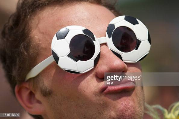 A festival goer wearing novelty sunglasses dances beside the Pyramid stage on the second day of the Glastonbury Festival of Contemporary Performing...