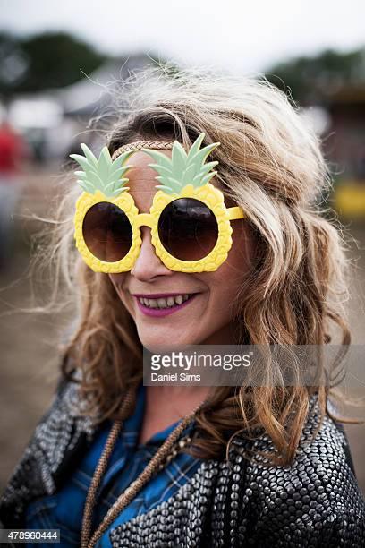 Festival goer wearing pineapple shaped sunglasses at the Glastonbury Festival at Worthy Farm Pilton on June 28 2015 in Glastonbury England