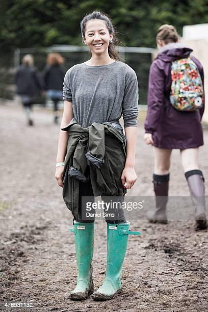 Festival goer wears a Zara top Northface coat Topshop trousers and Hunter wellies at the Glastonbury Festival at Worthy Farm Pilton on June 28 2015...