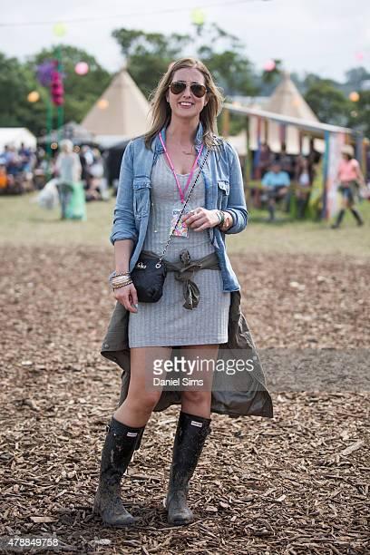 Festival goer wears an ASOS dress Mango denim shirt DKNY bag Hunter wellies and Rayban sunglasses at the Glastonbury Festival at Worthy Farm Pilton...