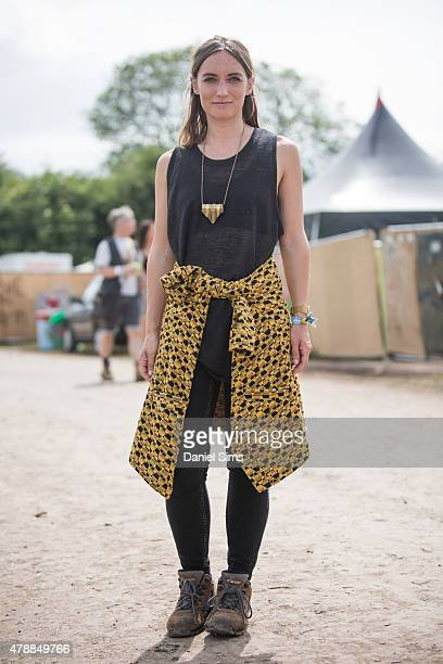 Festival goer wears an Urban Outfitters coat Topshop trousers and vintage necklace at the Glastonbury Festival at Worthy Farm Pilton on June 27 2015...
