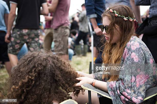A festival goer with a flower head band plays with a friends hair at the Glastonbury Festival at Worthy Farm Pilton on June 26 2015 in Glastonbury...