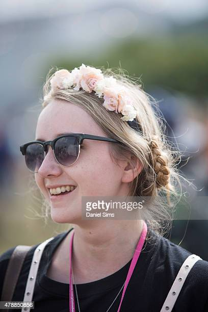Festival goer with a flower headband and platted hair at the Glastonbury Festival at Worthy Farm Pilton on June 27 2015 in Glastonbury England
