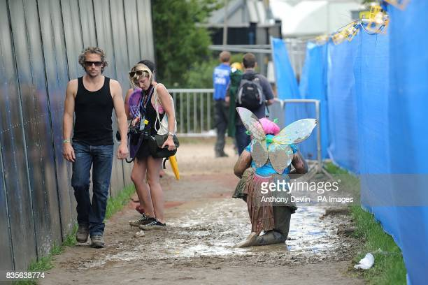 A festival goer with angel wings gets stuck in the mud at the 2009 Glastonbury Festival at Worthy Farm in Pilton Somerset