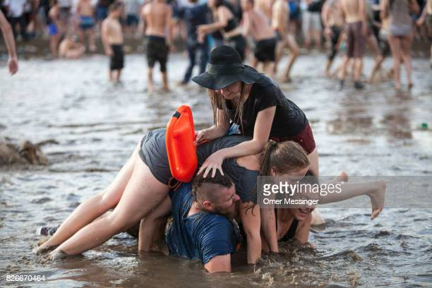 Festival goers are making a 'Man Pile' in a pool of muddy water at the 2017 Woodstock Festival Poland on August 4 2017 in Kostrzyn Poland The...
