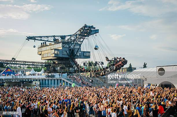 Festival goers are seen in front of an enormous excavator during Melt Festival on July 18 2015 in Graefenhainichen Germany
