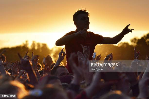 Festival goers at sunset during V Festival 2017 at Hylands Park on August 19 2017 in Chelmsford England