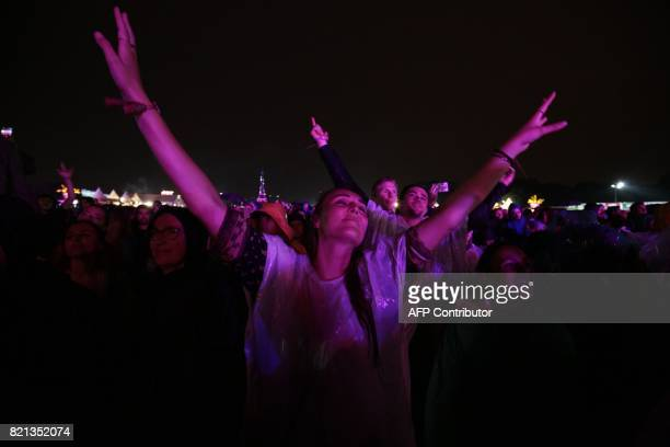 Festival goers attend the Lollapalooza music festival at the Longchamp Hippodrome in Paris on July 23 2017 / AFP PHOTO / GEOFFROY VAN DER HASSELT