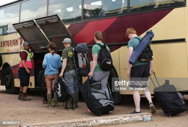 Festival goers boarding a coach at the bus station for transport leaving the Glastonbury Festival at Worthy Farm in Somerset