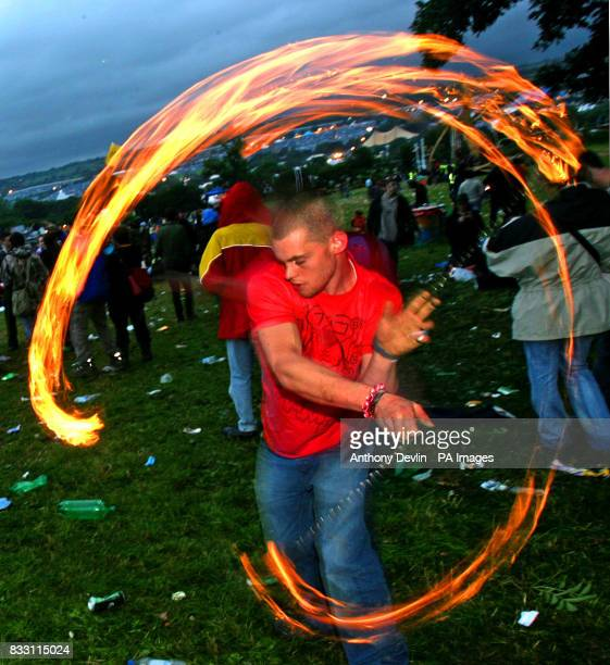 Festival goers celebrate the mid summer solstice at the stone circle at Worthy Farm in Pilton Somerset