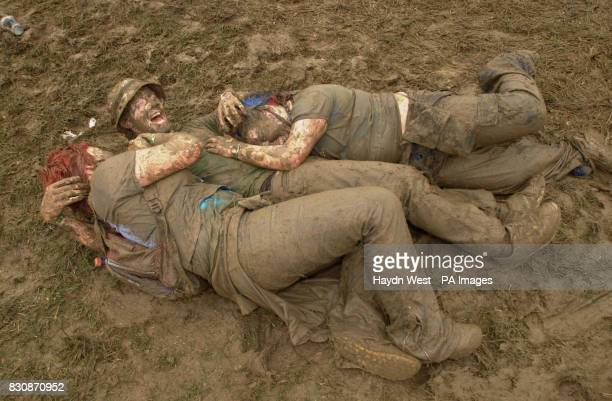 Festival goers coated with mud caused by overnight showers at a largely otherwise dry Witnness Rock Festival Fairyhouse Republic of Ireland where...