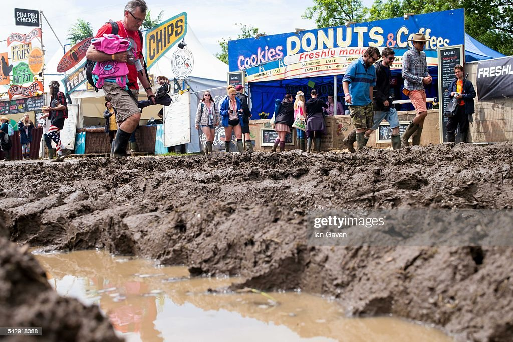 Festival goers cope with muddy conditions on day 2 of the Glastonbury Festival at Worthy Farm, Pilton on June 25, 2016 in Glastonbury, England. Now in its 46th year the festival is one largest music festivals in the world and this year features headline acts Muse, Adele and Coldplay. The Festival, which Michael Eavis started in 1970 when several hundred hippies paid just £1, now attracts more than 175,000 people.