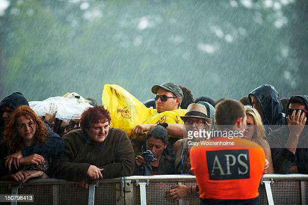 Festival goers endure the weather during the final day of Leeds Festival at Bramham Park on August 26 2012 in Leeds United Kingdom