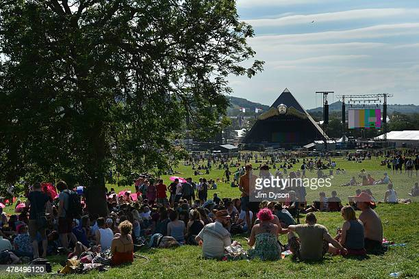 Festival goers enjoy the sun in front of the Pyramid stage at the Glastonbury Festival at Worthy Farm Pilton on June 25 2015 in Glastonbury England