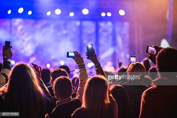 Festival goers filming a pop music concert