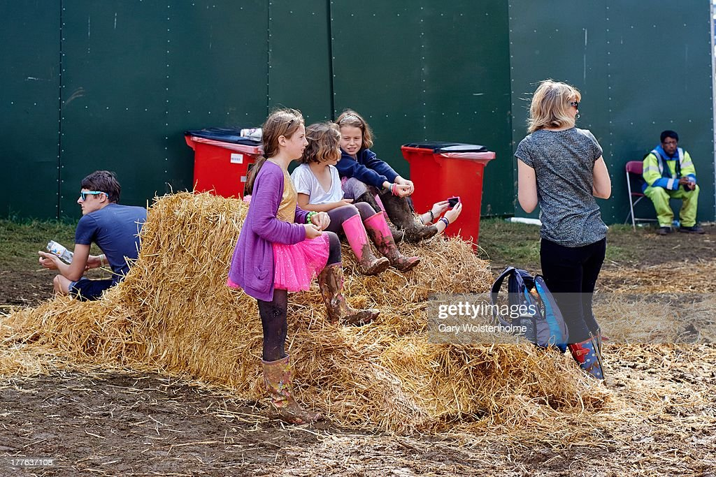 Festival goers gather round a hay bale placed to cover mud caused by heavy rain during Day 3 of Leeds Festival 2013 at Bramham Park on August 25, 2013 in Leeds, England.