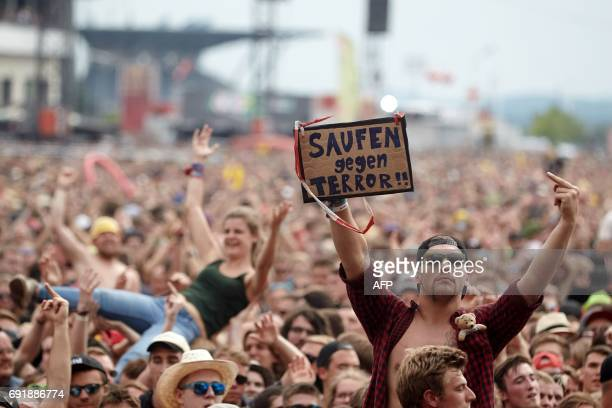 Festival goers hold a banner reading 'drinking instead of terror' at the 'Rock am Ring' music festival on June 3 2017 in Nuerburg during a...