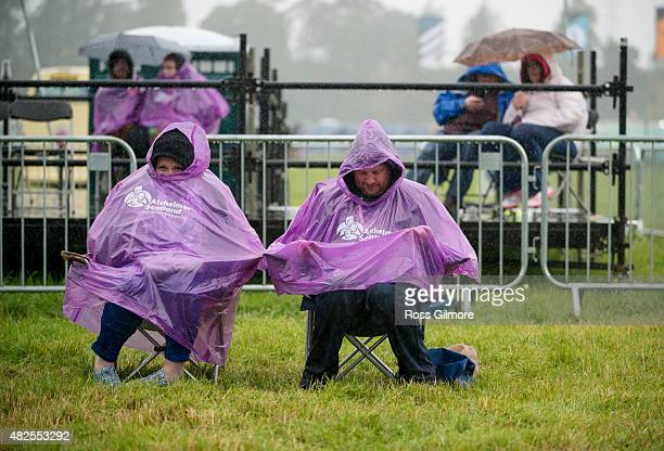 Festival goers in ponchos sit on camp chairs in the rain at the Aviemore Stopover festival on July 31 2015 in Aviemore Scotland