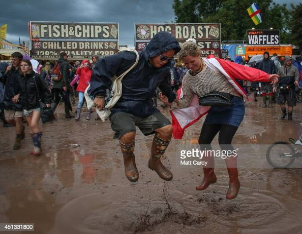 Festival goers jump in mud at Worthy Farm in Pilton during the 2014 Glastonbury Festival on June 27 2014 in Glastonbury England Gates opened on...