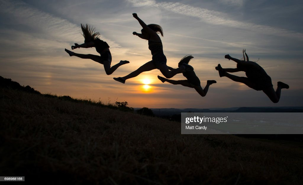 Festival goers jump in the air as they pose for a photograph as people gather to watch the sun set ahead of the gates opening to the public amid heightened security this year at the Glastonbury Festival site at Worthy Farm in Pilton on June 20, 2017 near Glastonbury, England. The largest greenfield festival in the world Glastonbury Festival is now a five-day festival of contemporary performing arts. The Somerset Festival, which Michael Eavis started in 1970 when several hundred hippies paid just £1, now attracts more than 175,000 people.