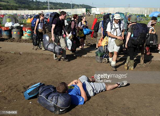 Festival goers make their way to the exits and the coach and bus station beyond as they begin to leave the Glastonbury Festival site on June 27 2011...