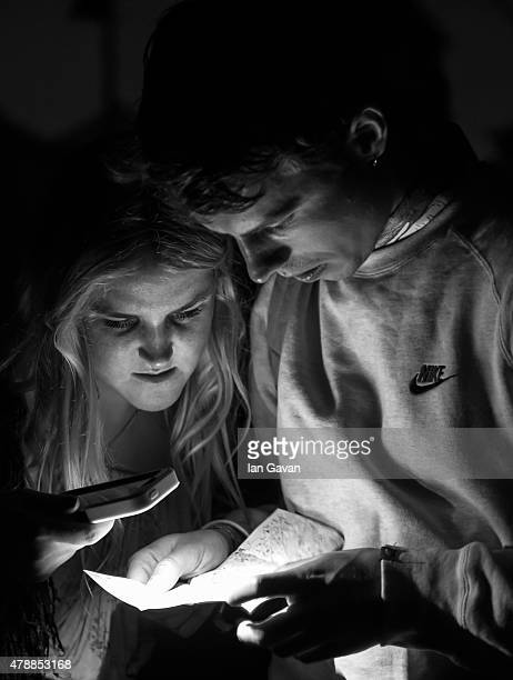 Festival goers read a map by torch light at the Glastonbury Festival at Worthy Farm Pilton on June 28 2015 in Glastonbury England Now its 45th year...