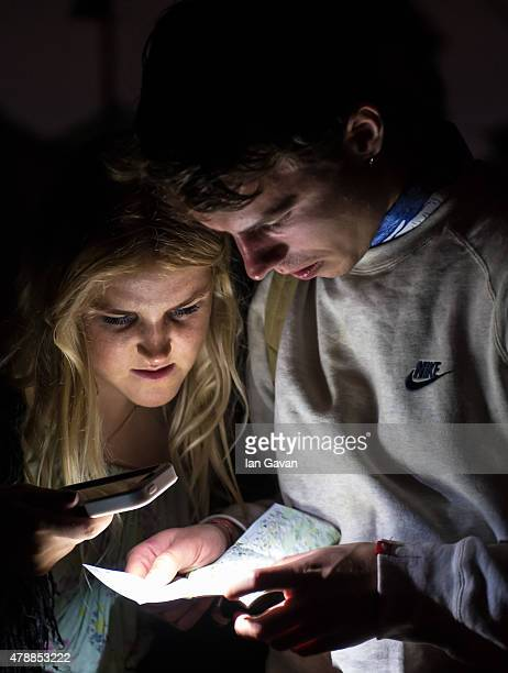 Festival goers read a map with the light from a mobile phone at the Glastonbury Festival at Worthy Farm Pilton on June 28 2015 in Glastonbury England...