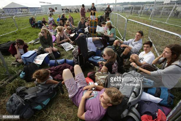 Festival goers resting at the bus station for transport leaving the Glastonbury Festival at Worthy Farm in Somerset