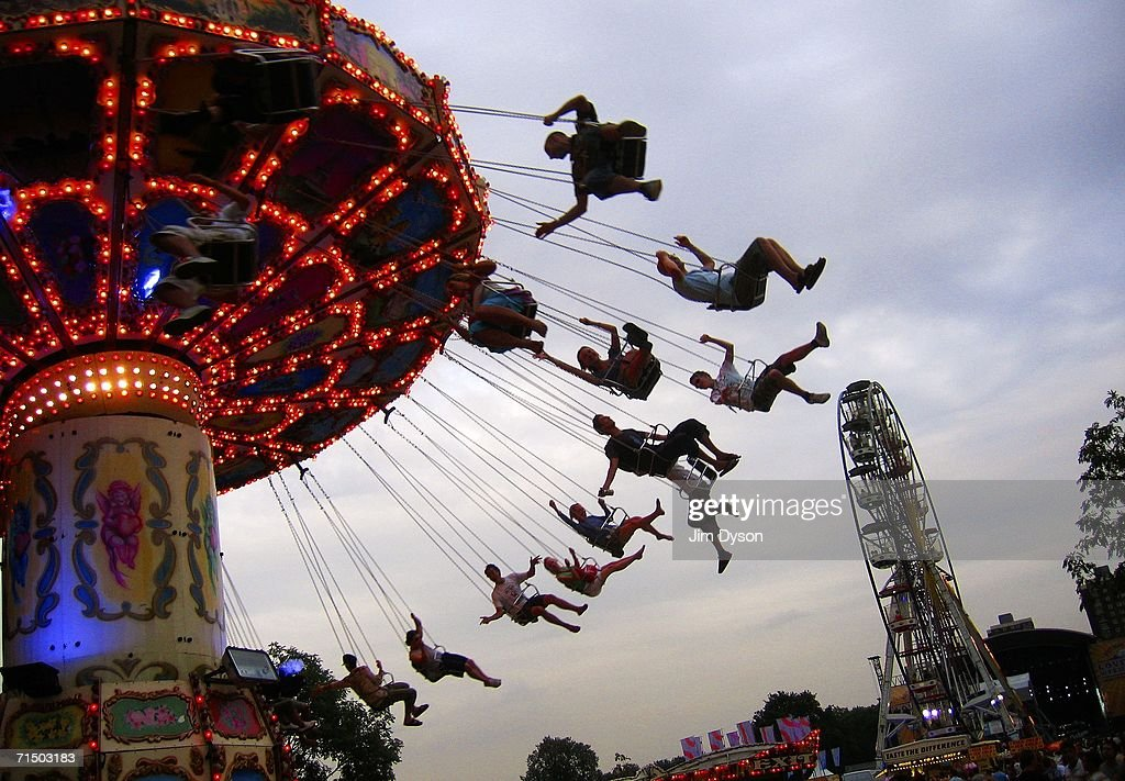 Festival goers ride a swing carousel at the fun fair during the first day of the Volvic Lovebox Weekender held in Victoria Park on July 22 2006 in...