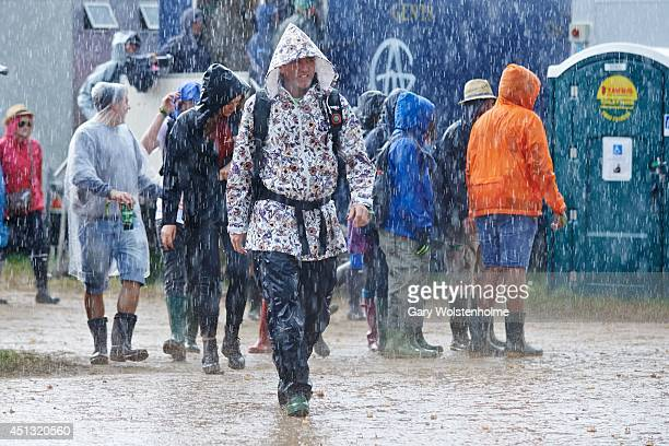 Festival goers run for cover as a thunderstorm hits the Glastonbury Festival at Worthy Farm on June 27 2014 in Glastonbury England
