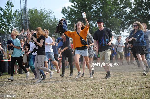 Festival goers run into the festival area as the gates of the annual Roskilde Festival open in Roskilde on July 5 2012 The festival runs till July 8...